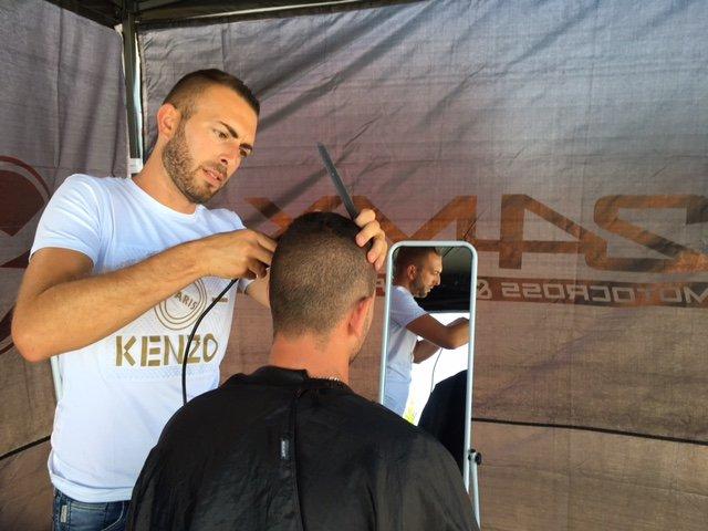 Bryan Dubief au coeur du marché de Chevigny St Sauveur avec son salon de coiffure en plein air.