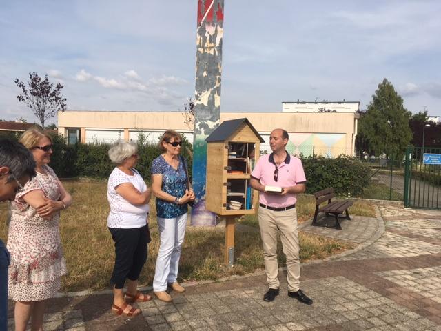 Inauguration de la boîte à livres à l'école du Breui, le maire livre à la main.
